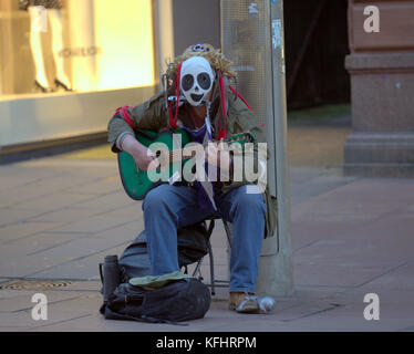 Glasgow, Scotland, UK. 29th October. Busker with green guitar and mask. Halloween on the streets of the city present - Stock Photo