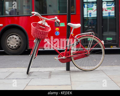 An elegant lady's red bicycle chained to a lampost in central London - Stock Photo