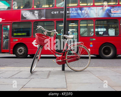 An elegant lady's red bicycle chained to a lampost in central London as a bus travels past in the background - Stock Photo