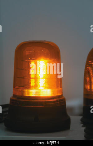 Glowing orange flasher stand alone in exhibition - Stock Photo