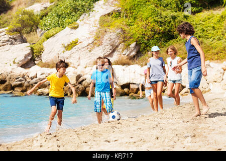 Group of boys play soccer on beach near the sea - Stock Photo