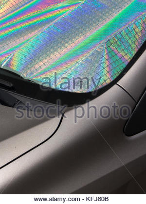 Car in Lisbon, Portugal. Sun protection on window with rainbow reflection. - Stock Photo