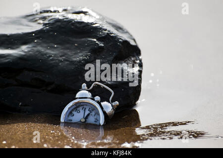 an abstract consept shot of a clock sinking in sand sorrounded by sea water currents meaning the passing of time - Stock Photo