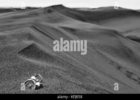 an abstract consept shot of a clock sinking in sand sorrounded by desert dunes meaning the passing of time - Stock Photo