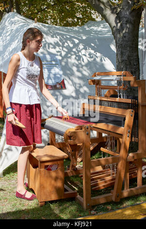 Folk market at Buda Castle Budapest - girl demonstrating hand weaving traditional Hungarian fabric on a manual loom - Stock Photo