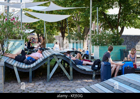 Relaxing on the undulating contemporary benches in the pop-up park Budapest - Stock Photo