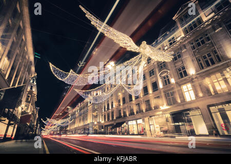 Regent Street Angels Holiday Lights with Double Decker Bus Light Trails in London, United Kingdom - Stock Photo
