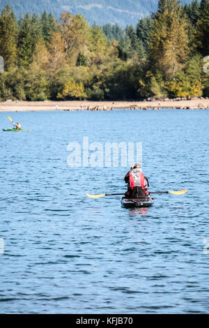 Kayakers in calm lake water on a sunny Autumn afternoon - Stock Photo