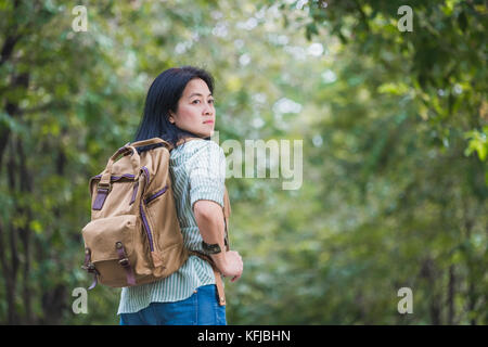 Happy young traveler woman backpacker travel in green natural forest ,greenery fresh air,Freedom wanderlust concept,Alone - Stock Photo