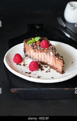 Slice of chocolate cheesecake decorated with almonds, raspberries and mint leaf on dark background. Vertical, selective - Stock Photo