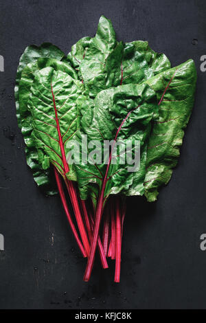 Fresh swiss chard leaves on black background. Table top view fresh organic green food - Stock Photo