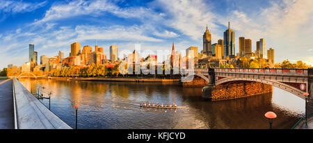 Warm golden light over Melbourne city CBD across Yarra river from Southbank between Walk foot bridge and Princes - Stock Photo