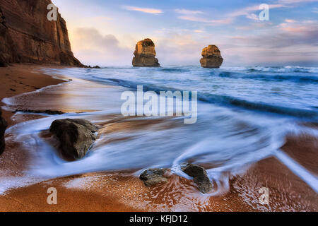 Sunrise at Gibson steps beach on Great Ocean road twelve apostles marine park with view of two standing rocks disconnected - Stock Photo