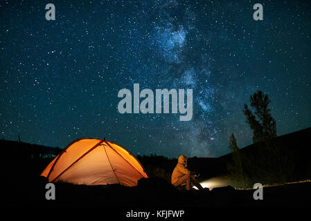 Man tourist near his camp tent at night. - Stock Photo