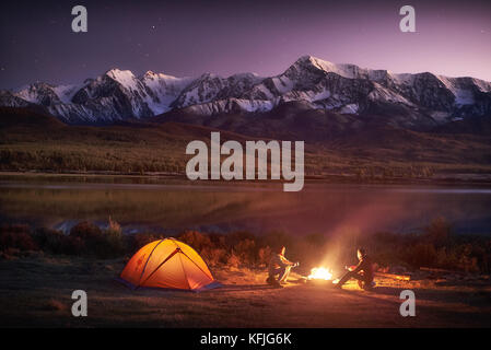Two men tourists sitting at the illuminated tent near campfire - Stock Photo