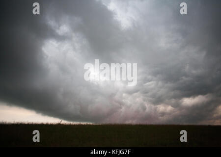gloomy sky over a field in nature - Stock Photo
