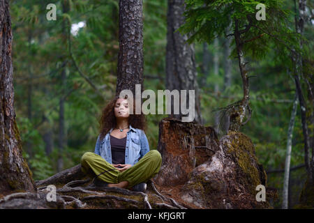 Young woman resting in a forest sitting in meditation posture leaning against a tree trunk in beautiful tranquil - Stock Photo