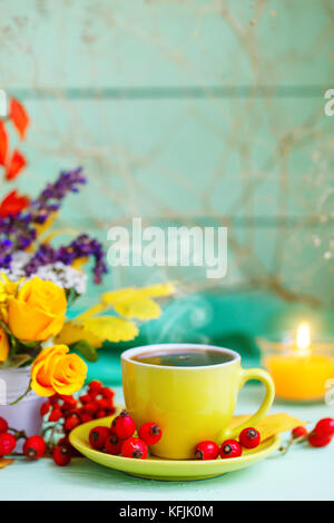 Cup of coffee, autumn leaves and flowers on a wooden table. Autumn still life. Selective focus. - Stock Photo