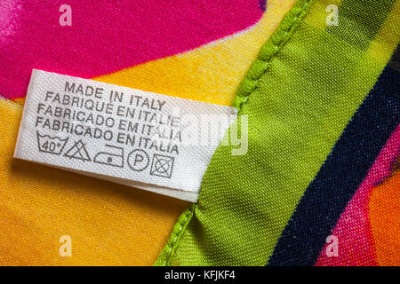 Label in woman's scarf made in Italy with care wash symbols - sold in the UK United Kingdom, Great Britain - Stock Photo