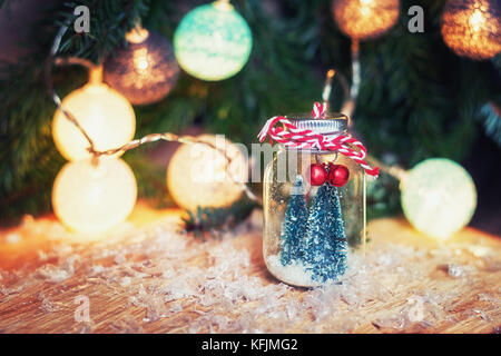 Two small art Christmas trees in a glass jar n front of a Christmas branch decorated with christmas balls - Stock Photo