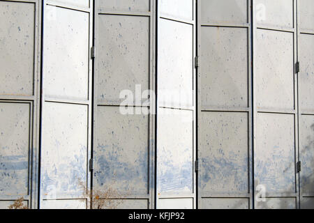 Old and damaged metal gray folding door on an abandoned warehouse ...