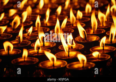 Burning candles in Buddhist temple. Dharamsala, Himachal Pradesh - Stock Photo