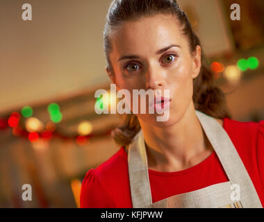 surprised young housewife in christmas decorated kitchen - Stock Photo