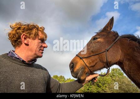 Close up portrait of horse whisperer / natural horsemanship practitioner holding brown warmblood horse outdoors - Stock Photo
