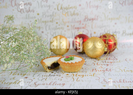 Christmas food photography image with glitter flowers red gold baubles and iced mince pies on white shiny festive - Stock Photo