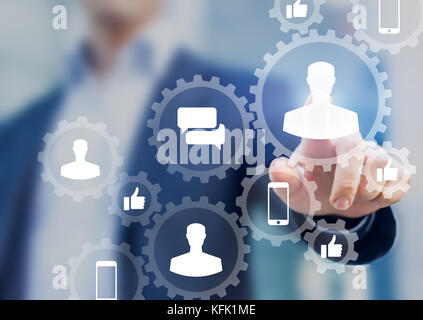 Social media digital marketing concept with icons of people profile, like, comment and smartphone inside connected gears network, businessman in backg