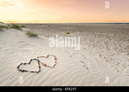 Pebbles arranged in shape of two hearts on sand beach ripples with beautiful sunset. - Stock Photo