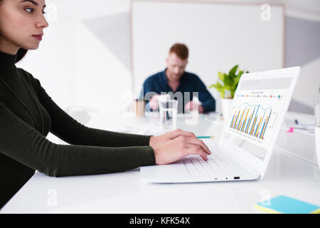 Girl works on a laptop with company statistics. Concept of internet sharing and interconnection - Stock Photo