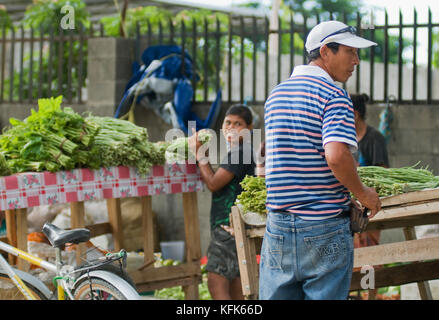 People sell a variety of fruits, vegetables, and other goods at a sidewalk market in Dili, Timor-Leste (East Timor) - Stock Photo