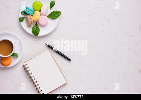 Cup of coffee with colorful macaron or macaroon with blank paper. Flat lay - Stock Photo