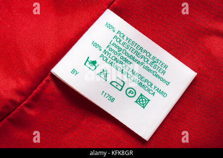 100% polyester lining 100% nylon label in woman's red clothing with wash care symbols instructions in different - Stock Photo