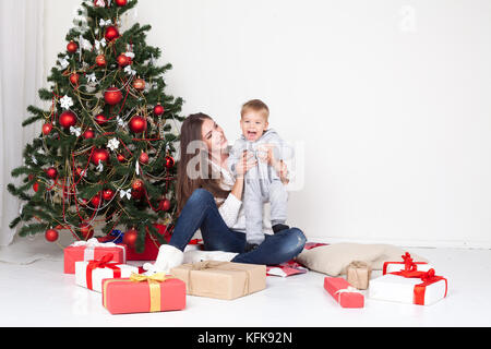 mother and son open gifts on Christmas and new year - Stock Photo
