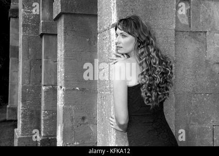 Lady looking around the columns on a portico - Stock Photo