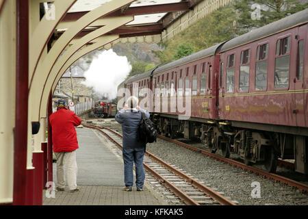 People photographing approaching steam locomotive at Blaenau Ffestiniog station on the Ffestiniog narrow gauge railway, - Stock Photo