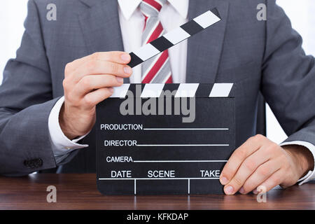 Midsection of businessman holding clapper board at desk - Stock Photo
