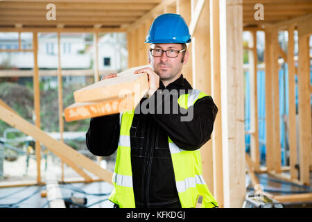 Carpenter Looking Away While Carrying Wood On Shoulder - Stock Photo