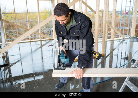 Young Carpenter Cutting Wood With Electric Saw At Site - Stock Photo