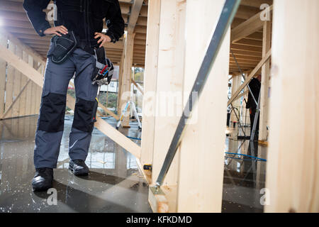 Carpenter Standing With Hands On Hips At Site - Stock Photo