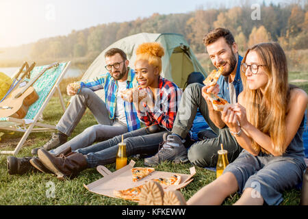 Friends eating pizza at the camping - Stock Photo