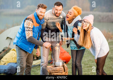 Friends in sweaters eating fondue outdoors - Stock Photo