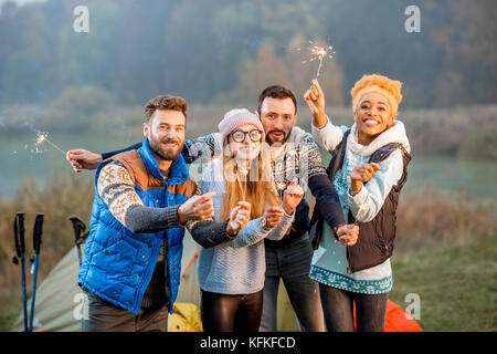 Friends in sweaters celebrating at the camping - Stock Photo