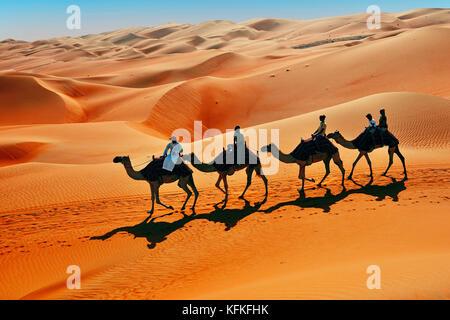 Tourists on camel ride in front of high sand dunes, sandy desert, Rub Al Khali, Emirate of Abu Dhabi, United Arab - Stock Photo