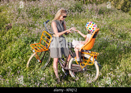 LOS ANGELES, CA – JULY 11: Woman rides a bicycle on a path over looking the ocean in Los Angeles, California on - Stock Photo