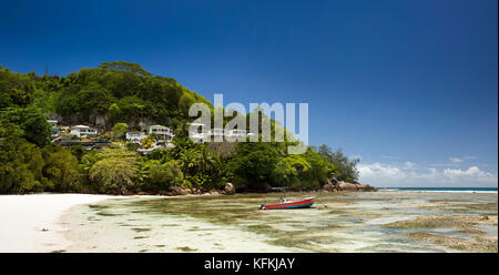 Sey247The Seychelles, Mahe, Baie Lazare, beach, boat in lagoon at low tide below properties on headland panoamic - Stock Photo
