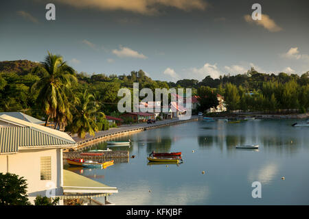 The Seychelles, Praslin, Baie St Anne, boats moored beside seafront road, early morning - Stock Photo