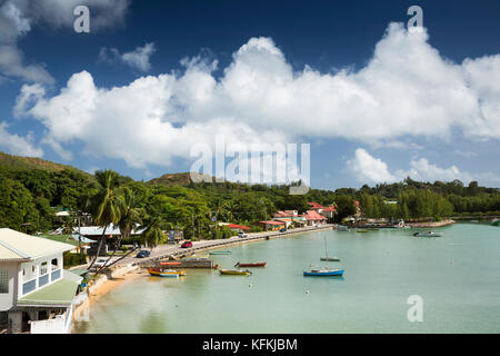 The Seychelles, Praslin, Baie St Anne, boats moored beside seafront road - Stock Photo